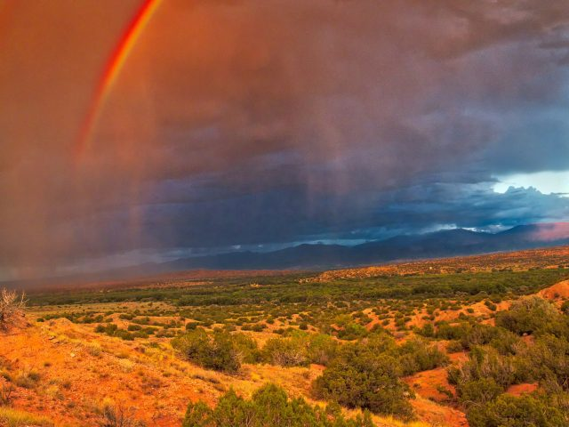 A double red rainbow shines brightly at sunset over Northern New Mexico