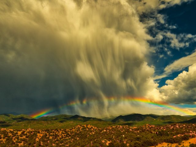 A low rainbow over Tesuque, New Mexico with curtains of falling rain.